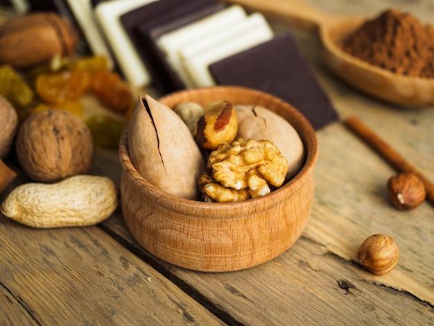 Noten in een houten beker op een houten tafel en andere zoetigheden.