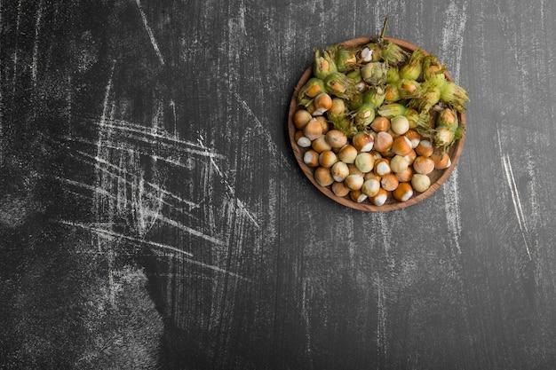 Noten in groene schelpen in een houten schotel