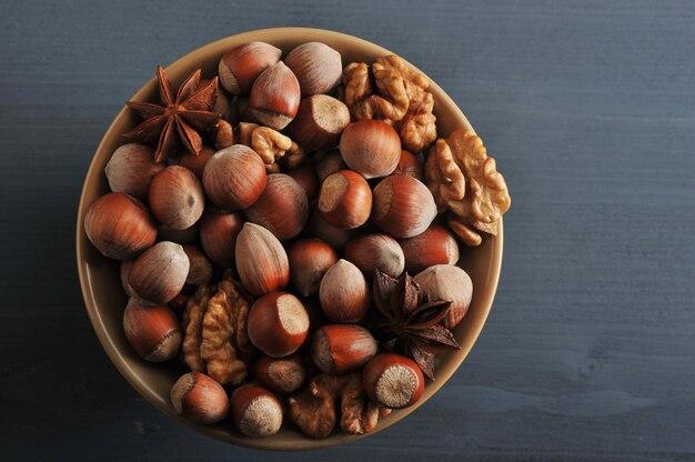 Noten in kom met hazelnoot in de schaal, gepelde walnoten, anijs