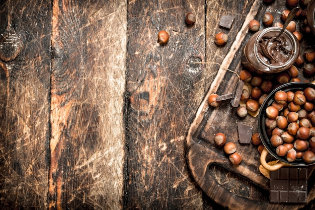Notenboter met chocolade en hazelnoten op houten achtergrond