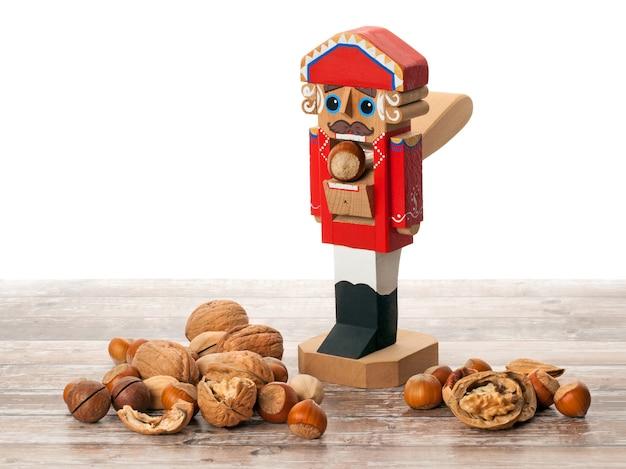 Notenkraker houten kerstspeelgoed met inshell en gebarsten noten op houten oppervlak met kopieerruimte