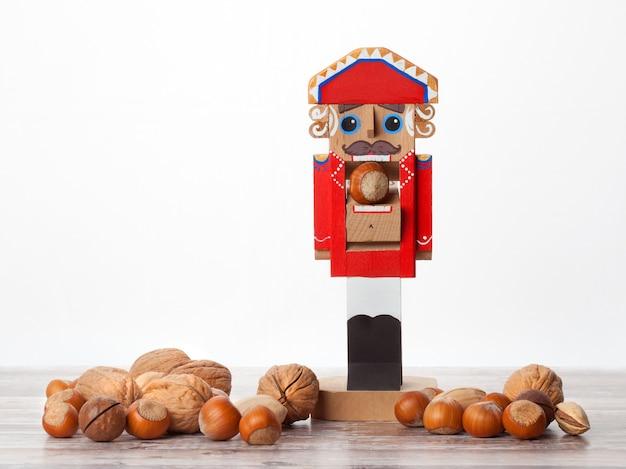 Notenkraker houten kerstspeelgoed met noten in de dop op houten oppervlak vooraanzicht met kopieerruimte