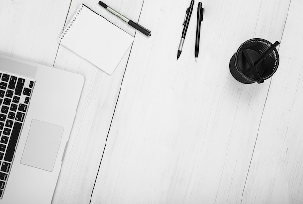 Notepad; pennen; houder en laptop op witte houten achtergrond
