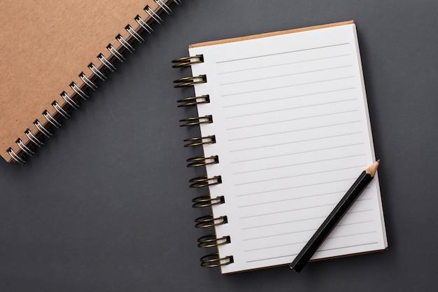 Notitie boek en pecil op zwarte achtergrond