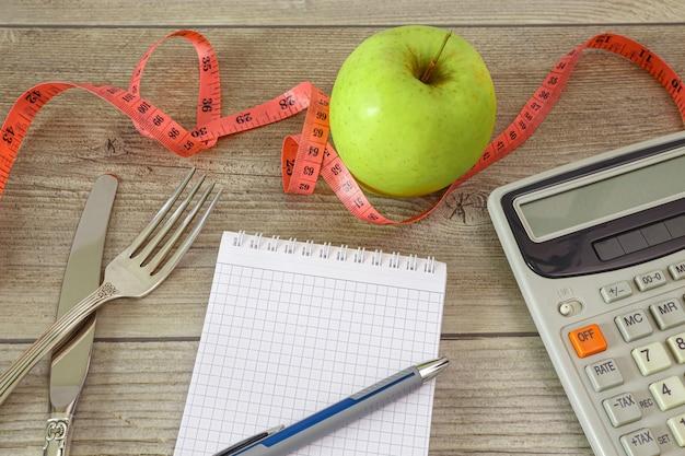Notitieblok met bestek en een rekenmachine voor het tellen van calorieën en een meetlint