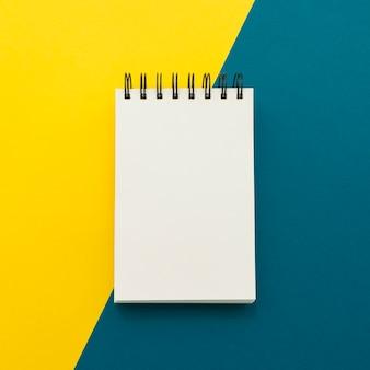 Notitieblok op gele en blauwe achtergrond