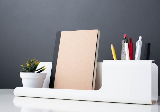 Notitieblok op moderne kantoorbenodigdheden op witte tafel.