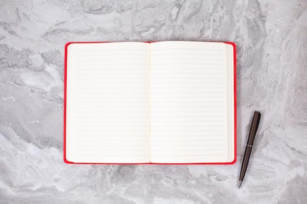 Notitieblok openen en zwarte pen op marmeren tafel. plat leggen