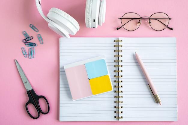 Notitieblok openen, gummen, pen, clips, schaar, brillen en koptelefoon op roze achtergrond