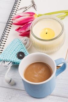 Notitieblok openen, koffie, kaars, oordoppen en tulp
