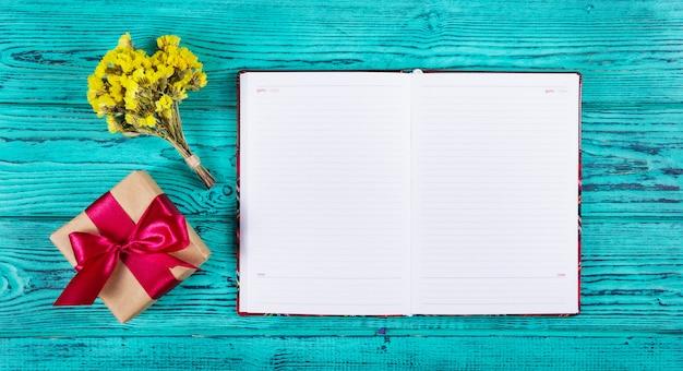 Notitieblok openen met blanco pagina's, geschenkdoos met lint en bloemen.