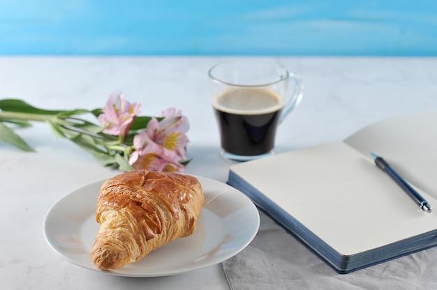 Notitieblok openen met bloemen en zwarte koffie en croissant
