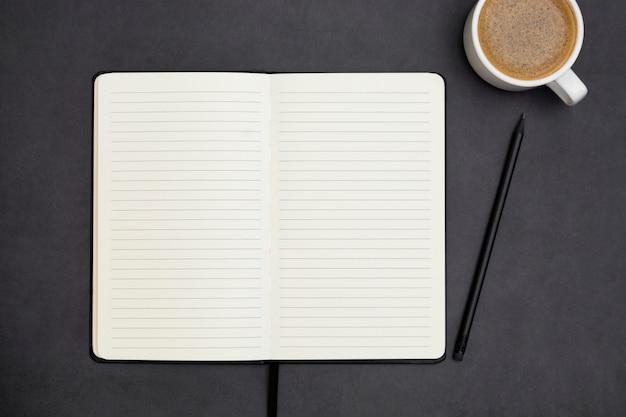 Notitieblok openen met lege pagina en koffiekopje. tafelblad, werkruimte op donkere achtergrond. creatief plat leggen.