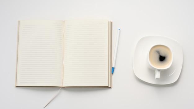 Notitieblok openen met lege witte lakens en een kopje koffie op een witte tafel, werkplek, bovenaanzicht