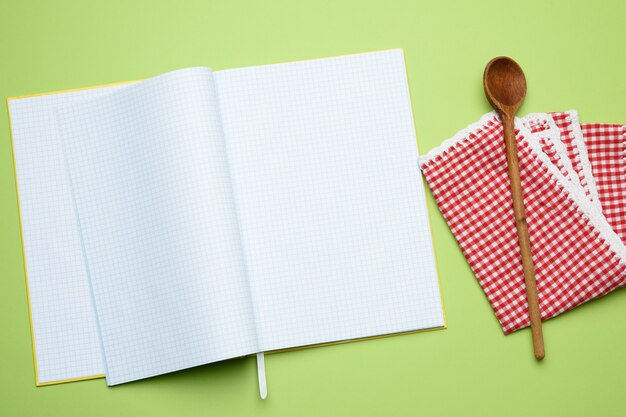 Notitieblok openen met lege witte lakens en houten lepel