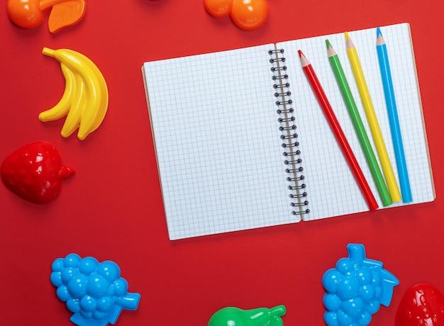 Notitieblok openen met lege witte vellen en veelkleurige houten potloden