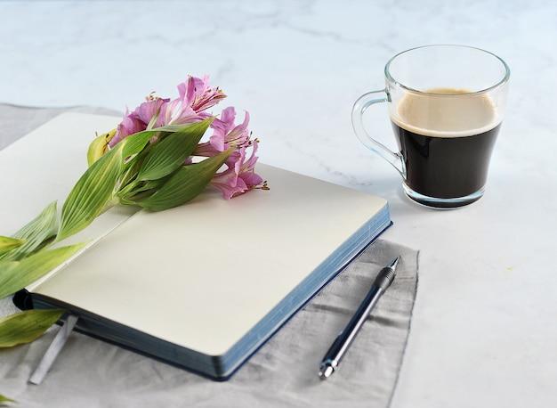 Notitieblok openen met lily bloemen en zwarte koffie