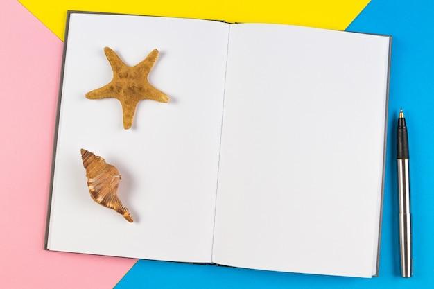 Notitieblok openen met schelpen en zeester op blauwe achtergrond