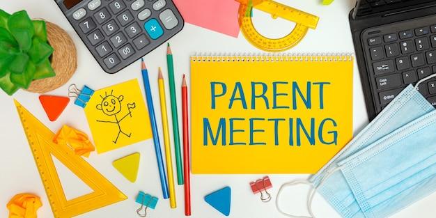 Notitieblok openen met schoolbenodigdheden en de inscriptie bovenliggende bijeenkomst