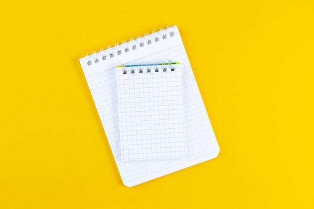 Notitieblok openen op helder geel papier achtergrond. schooltoebehoren met exemplaarruimte op kleurenachtergrond.