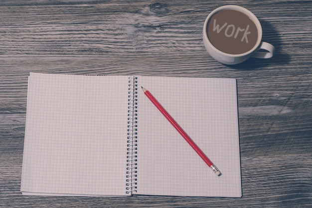 Notitieblok openen, potlood, kopje koffie met inscriptie