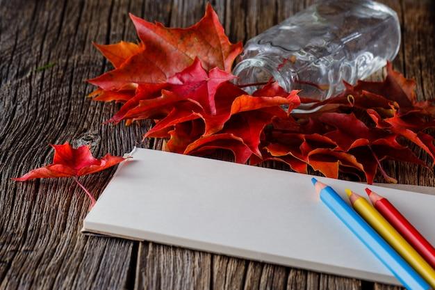 Notitieblok openen. vallen op bladeren op verweerde tafel