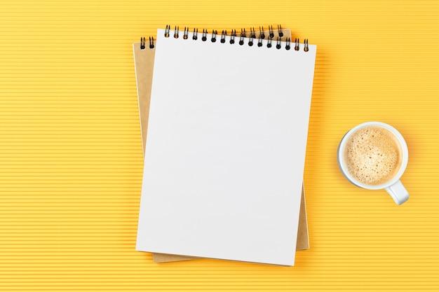 Notitieblok voor leerling met glazen en koffie op tafel op gele tafel. plat lag bedrijfsconcept.