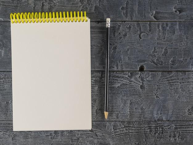 Notitieboek en zwart potlood op een donkere houten tafel. het uitzicht vanaf de top.