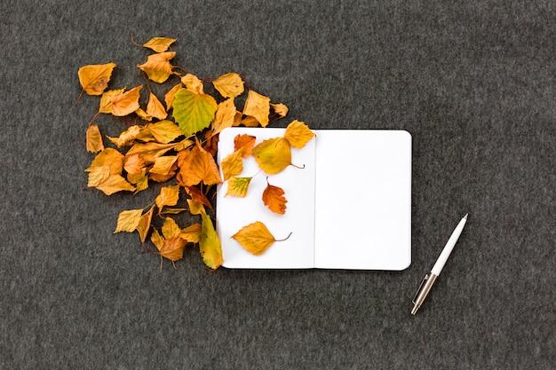 Notitieboek-, pen- en herfstbladeren op grijs