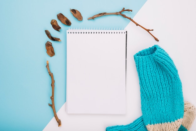 Notitieboekje dichtbij sokken en takjes