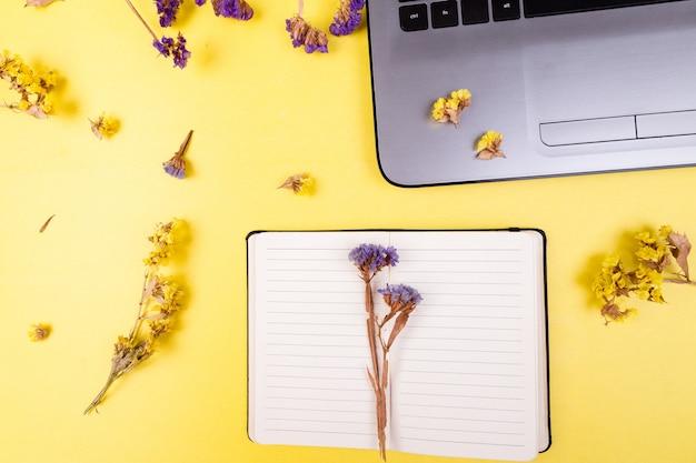 Notitieboekje en bloemen op geel