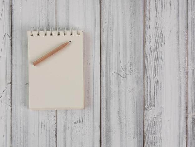 Notitieboekje en bruin potlood op houten lijst
