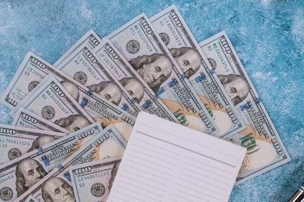 Notitieboekje en dollars op blauwe achtergrond.