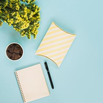 Notitieboekje en doos dichtbij muffin en bloemen