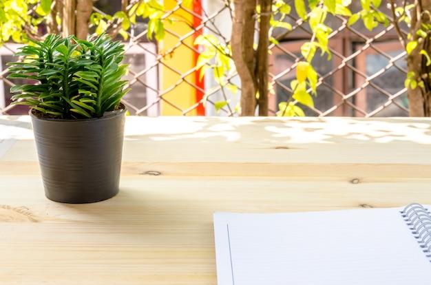 Notitieboekje en kleine boom op de houten lijst: zaken en onderwijs