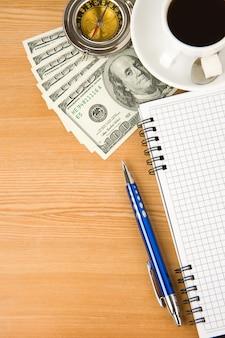 Notitieboekje en koffie met dollar op houten lijst