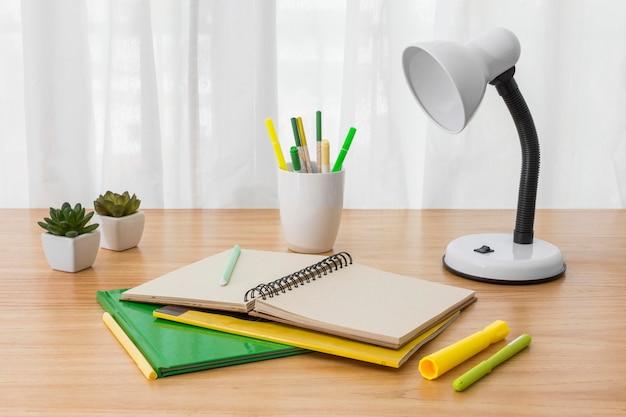 Notitieboekje en lamp op bureau hoge hoek