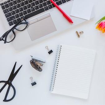 Notitieboekje en laptop dichtbij kantoorbehoeften op wit bureau