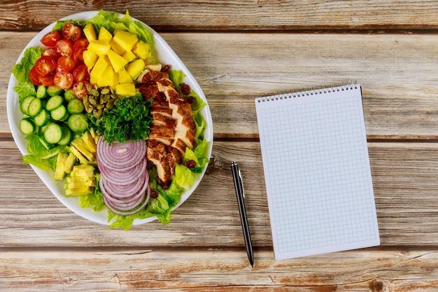Notitieboekje en pen met gezonde salade op houten lijst