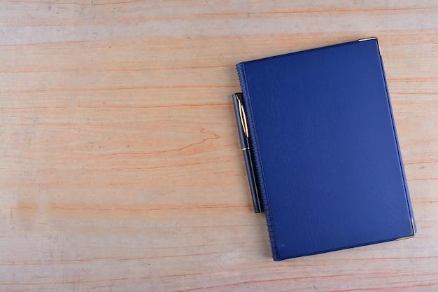 Notitieboekje en pen op een houten achtergrond