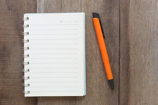 Notitieboekje en pen op oud hout voor de ontwerpachtergrond.