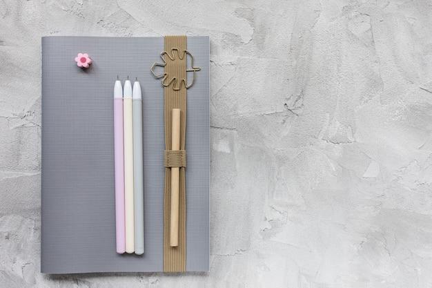 Notitieboekje en pennen op een grijze achtergrond.
