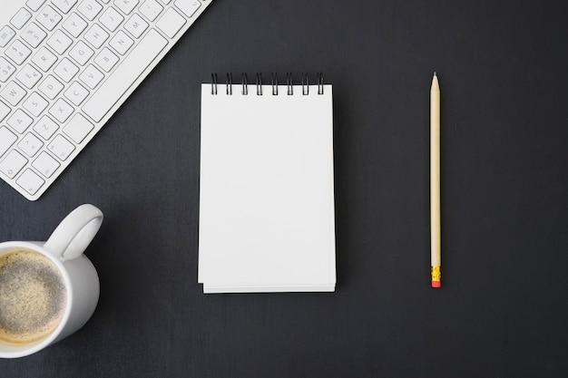 Notitieboekje en potlood met toetsenbord en koffie
