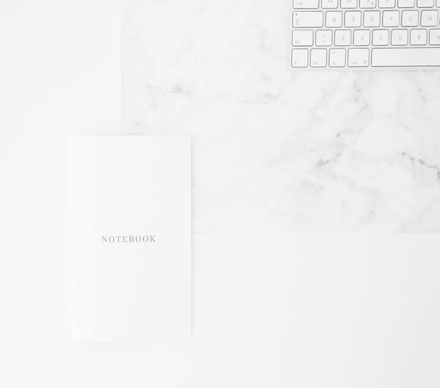Notitieboekje en toetsenbord op bureau tegen witte achtergrond