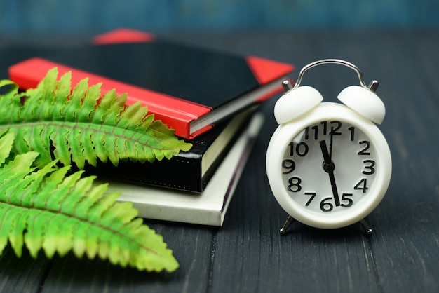 Notitieboekje en wekkerwekkerwit op een houten blauwe achtergrond