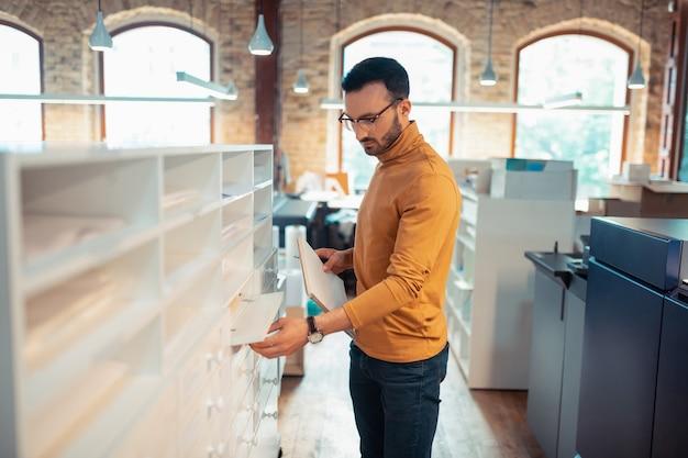 Notitieboekje houden. bebaarde donkerharige man met een bril die werkt in een drukkerij met een notitieboekje