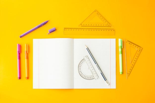 Notitieboekje in een cel onder pennen, potloden en heersers op een gele achtergrond