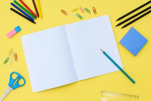 Notitieboekje in een kooi met een potlood, gum, liniaal, paperclips en andere kantoorbenodigdheden op een gele achtergrond. concept terug naar school. plaats voor tekst.