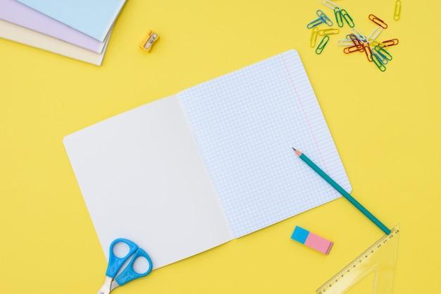 Notitieboekje in een kooi met een potlood, gum, liniaal, paperclips en schaar op een gele achtergrond. concept terug naar school. plaats voor tekst.