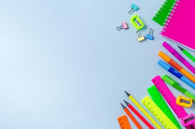 Notitieboekje, kleurpotloden, liniaal, pen, gum, puntenslijper en meer. school en kantoorbenodigdheden op blauwe achtergrond.